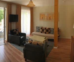 Wohnzimmer mit Sitzecke und TV - Pension am Weissen See